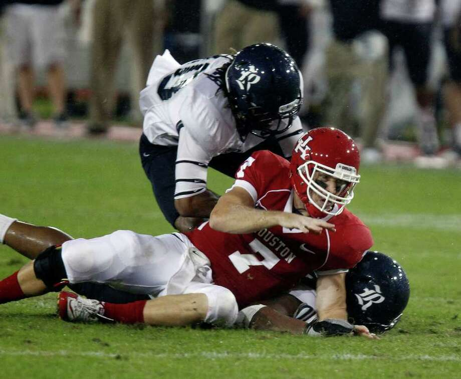 The University of Houston's quarterback Case Keenum is knocked to the ground by Rice University defenders during the first quarter of college football game action at Robertson Stadium Thursday, Oct. 27, 2011, in Houston. Photo: James Nielsen, Chronicle / © 2011 Houston Chronicle
