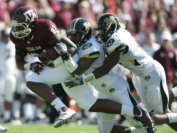 Texas A&M tight end Nehemiah Hicks (81) tries to run away from Missouri safety Kenji Jackson (13)