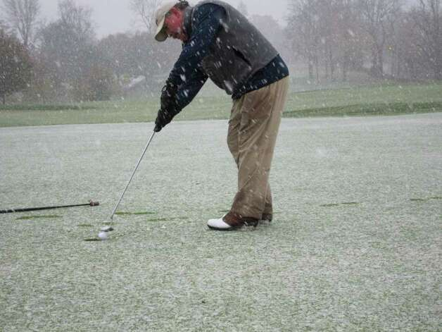 Patrick Dwyer, 51, of Glenbrook finishes a round of golf at Sterling Farms municipal golf course in Stamford as flurries from a nor'easter began to fall Saturday morning. Photo: Jonathan Lucas