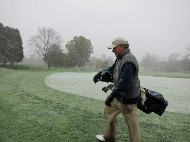Patrick Dwyer, 51, of Glenbrook finishes a round of golf at Sterling Farms municipal golf course in Stamford on Saturday morning as flurries of a nor'easter began to fall in the area. Photo: Jonathan Lucas