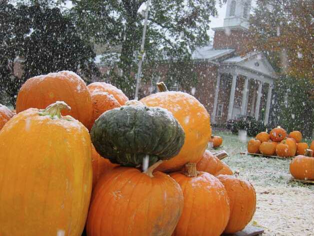 Snow falls on pumpkins for sale at St. John's Lutheran Church on Newfield Avenue in Stamford. Photo: Jonathan Lucas