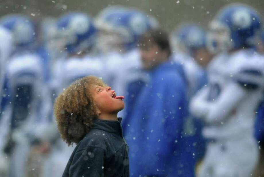 Eight-year-old Koy Price, of Norwalk, catches snowflakes on his tongue on the sidelines of the Staples vs. Darien football game Saturday, Oct. 29, 2011 in Westport, Conn. Photo: Autumn Driscoll / Connecticut Post