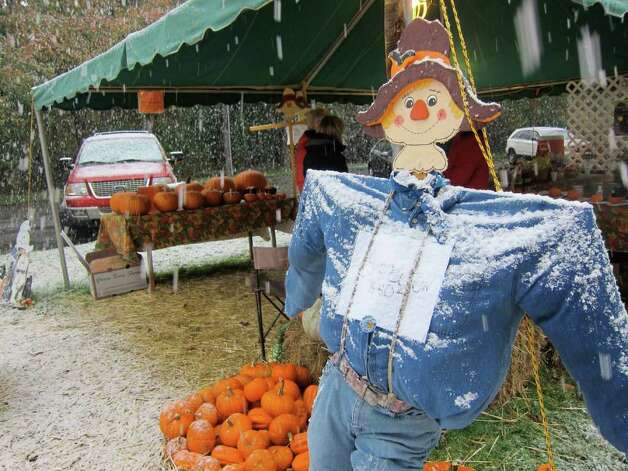 Gayle Hartfelder, Jody VanHouten, Mary Lupo and Leslie Loop volunteer at a pumpkin patch sale at St. John's Lutheran Church on Newfield Avenue as snow began to fall Saturday morning. Photo: Jonathan Lucas