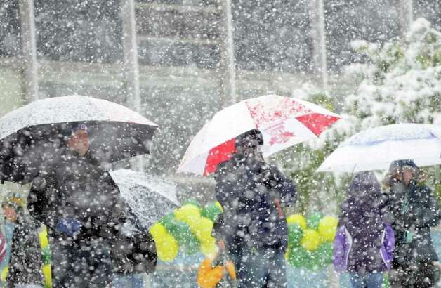 Spectators of the Trinity Catholic High School football game seek shelter under umbrellas during a snow storm in Stamford on Saturday, Oct. 29, 2011. Photo: Amy Mortensen / Connecticut Post Freelance