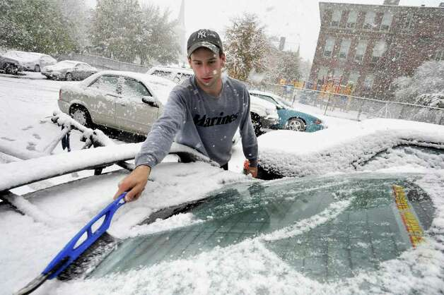 Nick Neuner, of Brewster, N.Y., clears snow from his car Saturday, Oct. 29, 2011. Photo: Michael Duffy