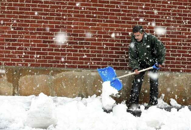 Gilmer de Sousa shovels snow from the walkway of a Danbury business Saturday, Oct. 29, 2011. Photo: Michael Duffy