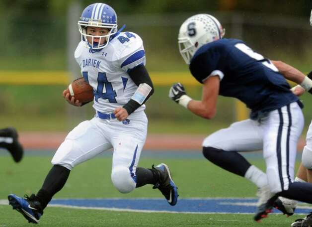 Darien's Christian Bognar carries the ball as Staples' Nick Kelly defends Saturday, Oct. 29, 2011 during their football game in Westport, Conn. Photo: Autumn Driscoll / Connecticut Post