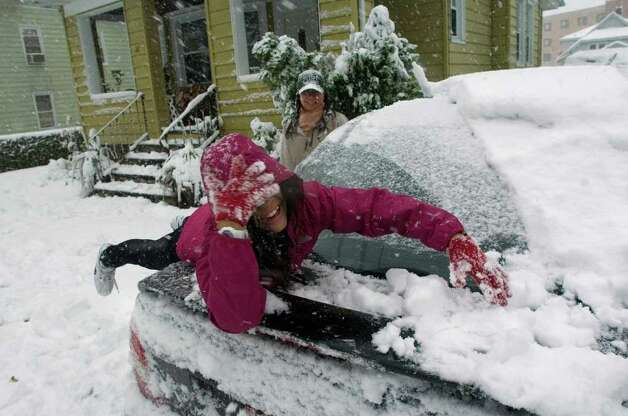 Grace Somkhoun, 10, helps Mae Pacete clear the snow from her car in Danbury on Saturday, Oct. 29, 2011. This is their first big snow after moving to Danbury from North Carolina. Photo: Jason Rearick / The News-Times