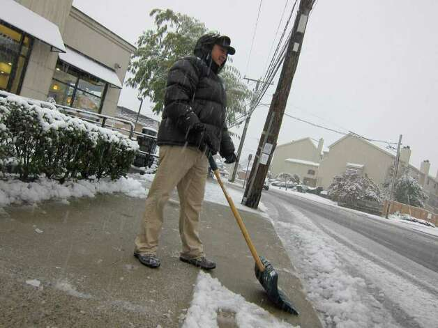 Francisco Chinchilla, 24, clears snow in front of Donuts Delight on Hope Street in Stamford. Photo: Jonathan Lucas