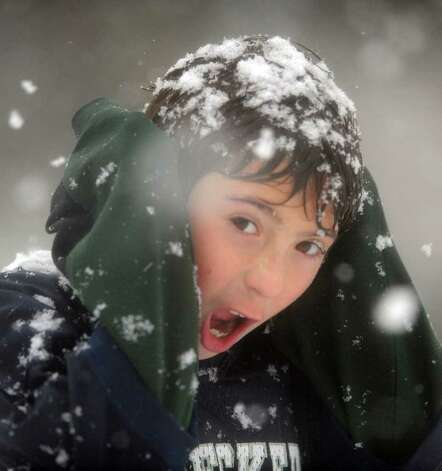 Ten-year-old Adam Petro, of Westport, shields his ears from the wind on the sidelines of the Staples vs. Darien football game Saturday, Oct. 29, 2011 in Westport, Conn. Photo: Autumn Driscoll / Connecticut Post