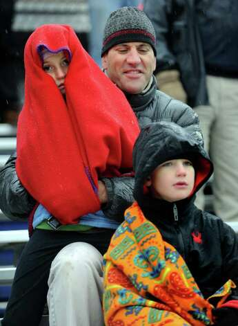Ten-year-old Honor Heisler tries to stay warm under a blanket while watching the Staples vs. Darien football game with her father Matt Heisler and seven-year-old brother, William, Saturday, Oct. 29, 2011 in Westport, Conn. Photo: Autumn Driscoll / Connecticut Post