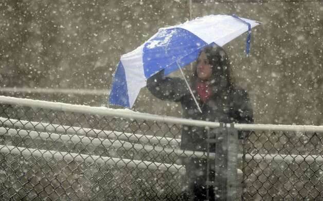 Fans watch the Staples vs. Darien football game under falling snow Saturday, Oct. 29, 2011 in Westport, Conn. Photo: Autumn Driscoll / Connecticut Post