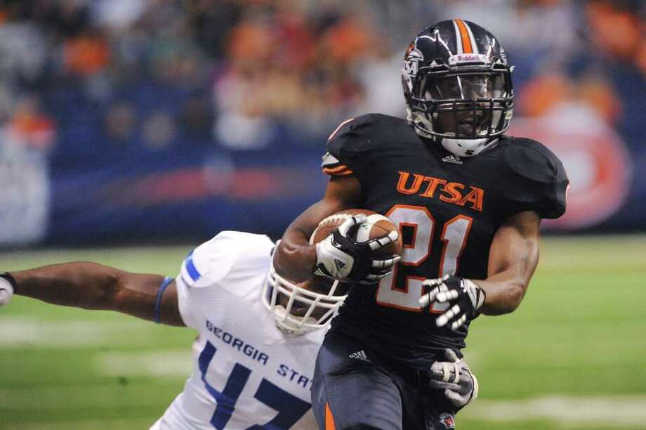 UTSA's Chris Johnson (21) runs for yardage after a reception as Michael Hall of Georgia State runs him down during first-half college football action at the Alamodome on Saturday, Oct. 29, 2011. BILLY CALZADA / gcalzada@express-news.net