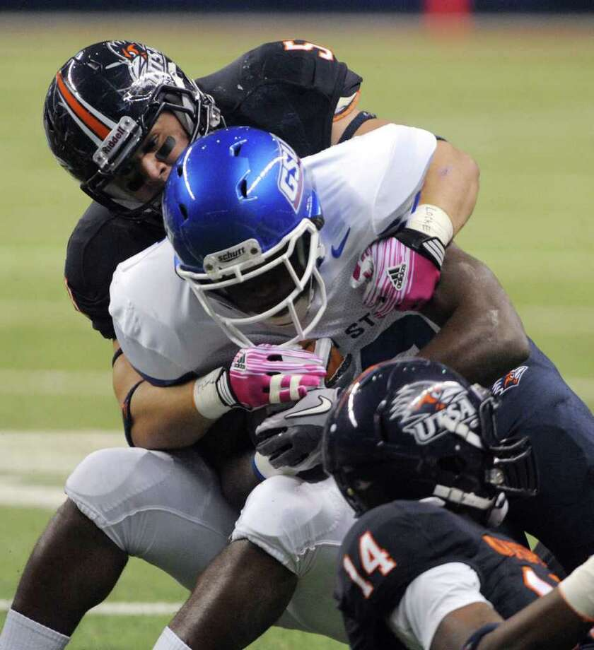 UTSA linebacker Brandon Reeves, top, tackles Donald Russell of Georgia State during first-half college football action at the Alamodome on Saturday, Oct. 29, 2011. BILLY CALZADA / gcalzada@express-news.net