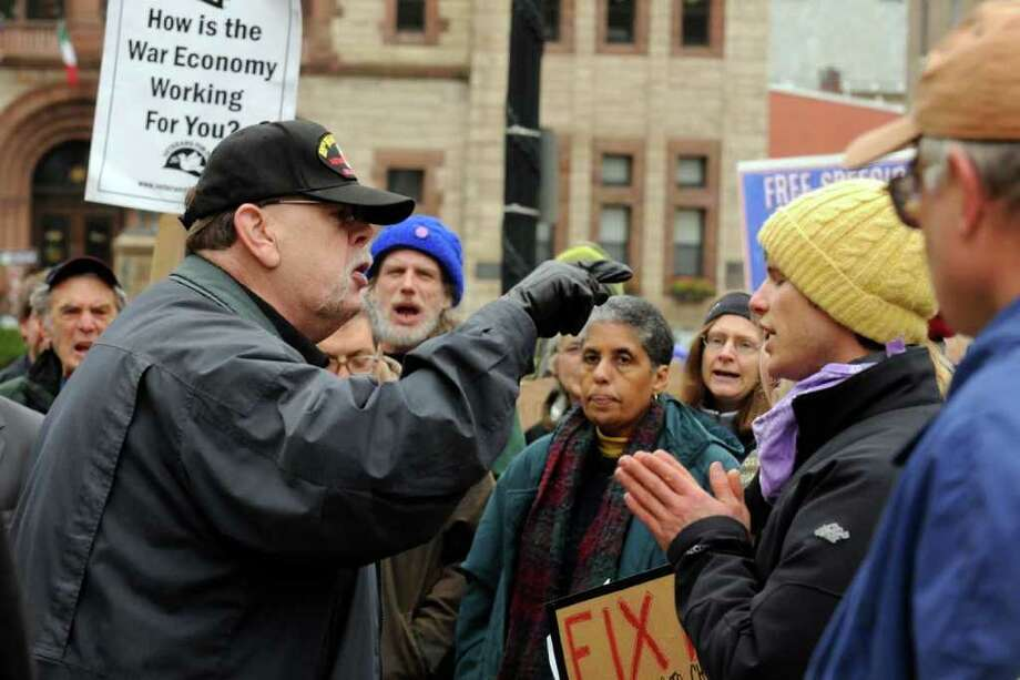 Alfred Davis,left, trys to argue with Daniel Morrissey of Latham a Occupy Albany participant on Washigton Avenue across from the Capitol in Albany , NY Saturday, Oct. 29, 2011.( Michael P. Farrell/Times Union) Photo: Michael P. Farrell