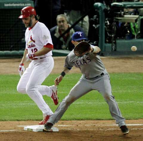 St. Louis Cardinals' Lance Berkman is safe at first as Texas Rangers' Michael Young catches the ball during the seventh inning of Game 7 of baseball's World Series Friday, Oct. 28, 2011, in St. Louis. (AP Photo/Jeff Roberson) Photo: Associated Press