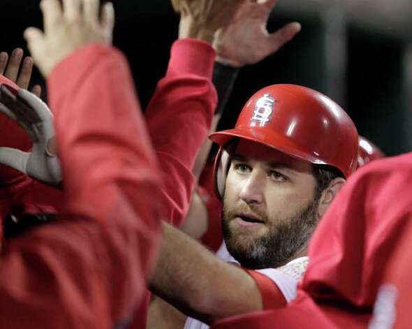 St. Louis Cardinals' Lance Berkman is congratulated in the dugout after hitting a two-run home run during the first inning of Game 6 of baseball's World Series against the Texas Rangers Thursday, Oct. 27, 2011, in St. Louis. (AP Photo/Charlie Riedel) Photo: Associated Press