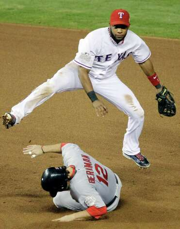 Texas Rangers' Elvis Andrus leaps over St. Louis Cardinals' Lance Berkman (12) to turn a double play on a ball hit by David Freese during the fifth inning of Game 4 of baseball's World Series Sunday, Oct. 23, 2011, in Arlington, Texas. (AP Photo/Paul Sancya) Photo: Associated Press