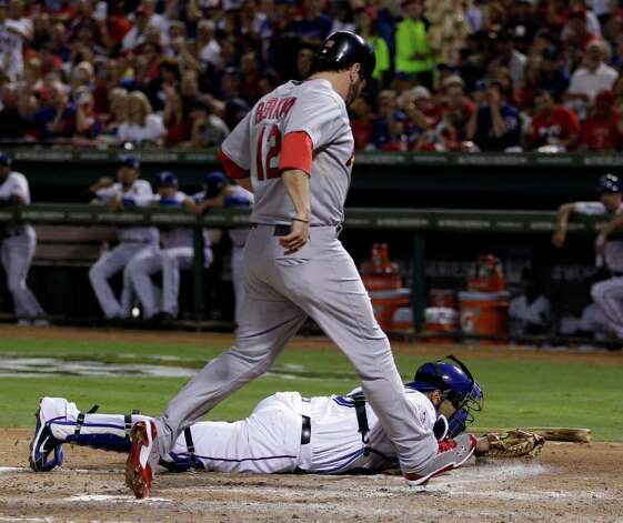 St. Louis Cardinals' Lance Berkman (12) scores after Texas Rangers catcher Yorvit Torrealba couldn't handle a throw during the fourth inning of Game 3 of baseball's World Series Saturday, Oct. 22, 2011, in Arlington, Texas. (AP Photo/Matt Slocum) Photo: Associated Press