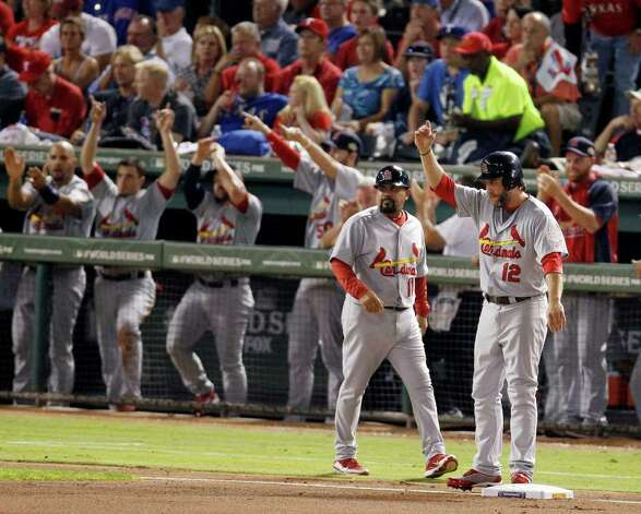As St. Louis Cardinals' Jose Oquendo (11) walks over Lance Berkman (12) reacts to David Freese's RBI double during the fourth inning of Game 3 of baseball's World Series against the Texas Rangers Saturday, Oct. 22, 2011, in Arlington, Texas. (AP Photo/Eric Gay) Photo: Associated Press