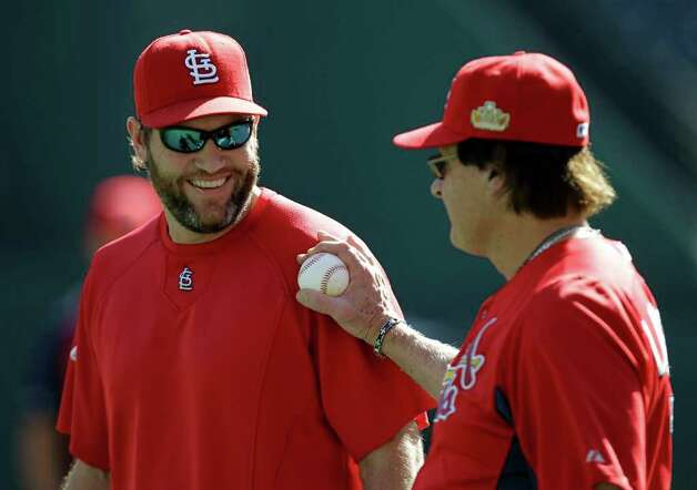 St. Louis Cardinals' Lance Berkman, left, smiles as he talks with manager Tony La Russa during practice Friday, Oct. 21, 2011, in Arlington, Texas. The Cardinals will play the Texas Rangers in Game 3 of baseball's World Series on Saturday. (AP Photo/Tony Gutierrez) Photo: Associated Press
