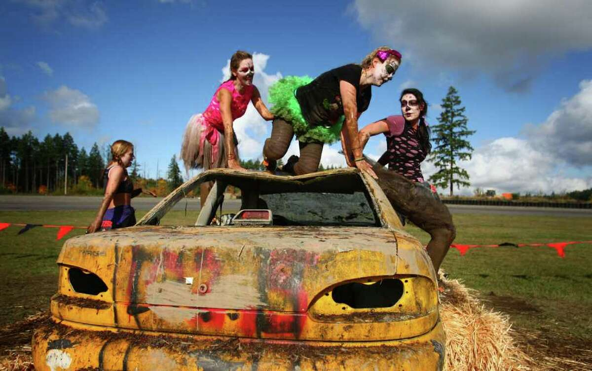 Competitors dressed as 'zombies' climb an obstacle during the Gladiator Rock'N Run at Pacific Raceways in Kent. Participants in the 5k race ran through obstacles that included an ice bath, mud pit and had to leap over fire.
