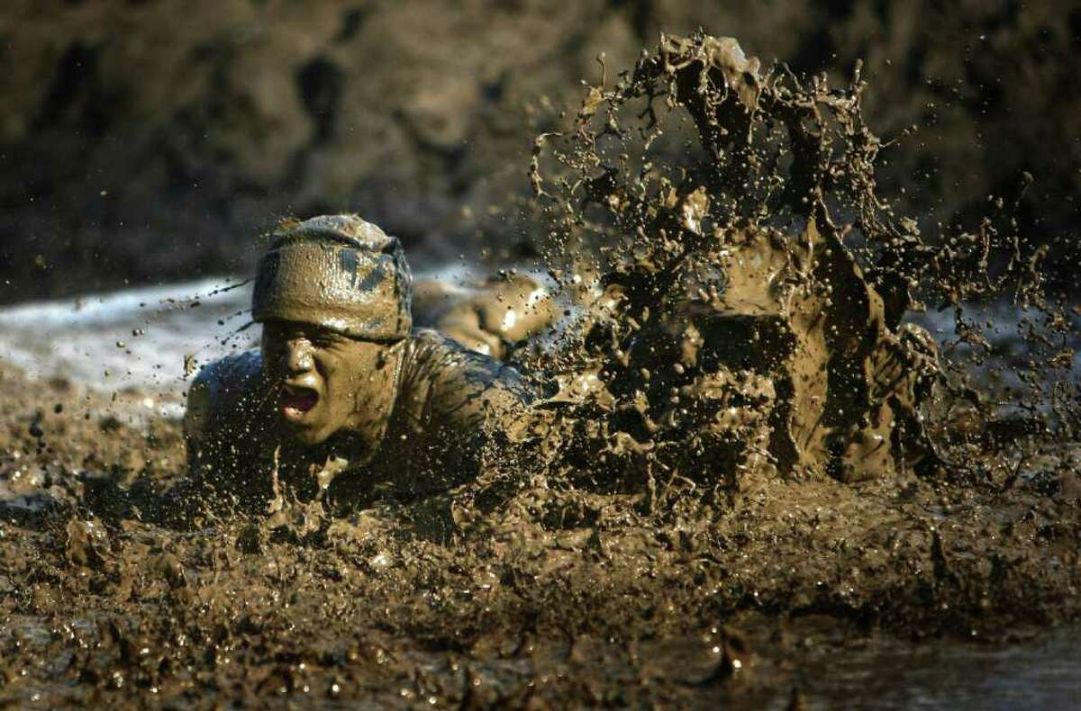 A participant leaps into a mud pit during the Gladiator Rock'N Run at Pacific Raceways in Kent. Participants in the 5k race ran through obstacles that included an ice bath, mud pit and had to leap over fire.