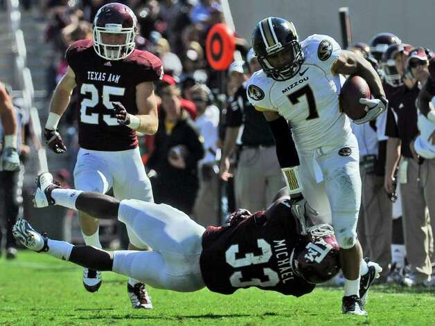 Texas A&M running back Christine Michael (33) goes horizontal after Missouri defensive back Randy Ponder (7) as Ryan Swope (25) follows after Ponder intercepted a pass during the second half of an NCAA college football game Saturday, Oct. 29, 2011, in College Station, Texas. Missouri won in overtime 38-31. Photo: AP