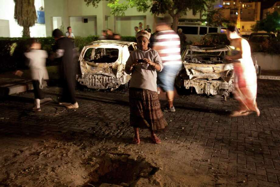 A woman uses her phone to take a photograph at a site where a rocket fired from the Gaza Strip hit Ashdod, southern Israel, Saturday, Oct. 29, 2011.  Israeli aircraft struck at Palestinian militants on Saturday who responded with a volley of rockets which rained on southern Israeli towns, Israeli and Palestinian officials said. Palestinian sources said that seven militants were killed while the Israelis reported several civilians injured. Photo: Ariel Schalit, AP / AP