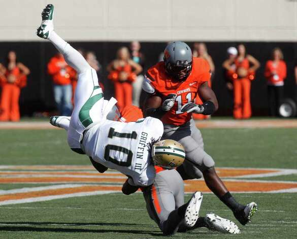 Baylor quarterback Robert Griffin III (10) is upended by Oklahoma State safety Markelle Martin, bottom, as linebacker Shawn Lewis (11) moves in at rear during the first quarter of an NCAA college football game in Stillwater, Okla., Saturday, Oct. 29, 2011. Photo: AP