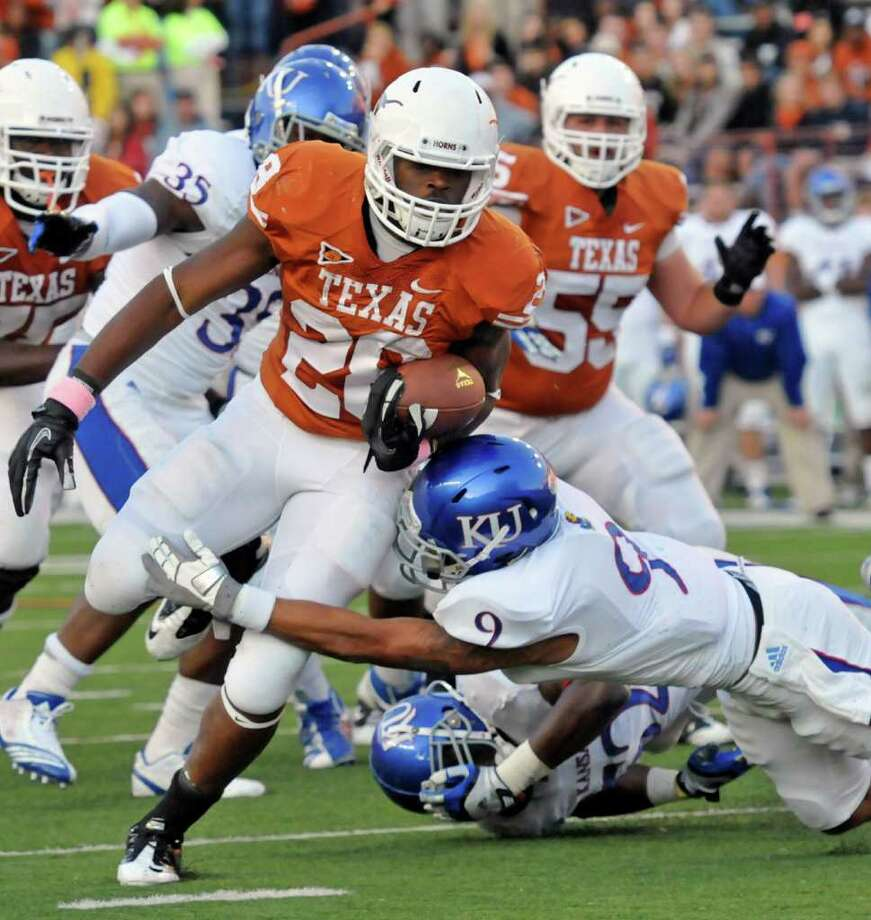 Texas running back Malcolm Brown (28) breaks the tackle of Kansas safety Keeston Terry (9) to score a touchdown during the first quarter of an NCAA college football game, Saturday, Oct. 29, 2011, in Austin, Texas. (AP Photo/Michael Thomas) Photo: Michael Thomas, Associated Press / FR65778 AP