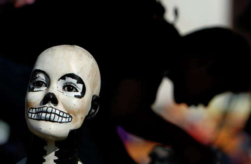 A doll's head, painted as a skull, sits on an offering as part of Day of the Dead celebrations at Me