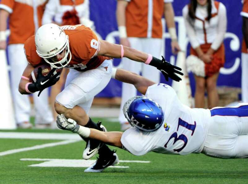 Texas' Jaxon Shipley, left, is tackled by Kansas' Ben Heeney, right, as he tries to return a punt