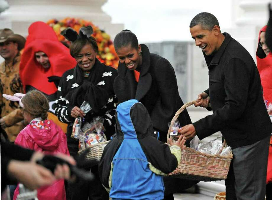US President Barack Obama, First Lady Michelle Obama (2nd R) and her mother Marian Robinson offer treats to trick-or-treaters October 29, 2011 on the North Portico of the White House in Washington, DC. Photo: MANDEL NGAN, Getty / AFP