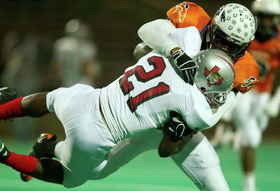 Bush linebacker Henry Offiah (50) makes a stop on Travis running back Michael Igwe (21) during the first quarter of a high school football game at  Mercer Stadium, Saturday, Oct. 29, 2011, in Sugar Land. Photo: Smiley N. Pool, Houston Chronicle / © 2011  Houston Chronicle