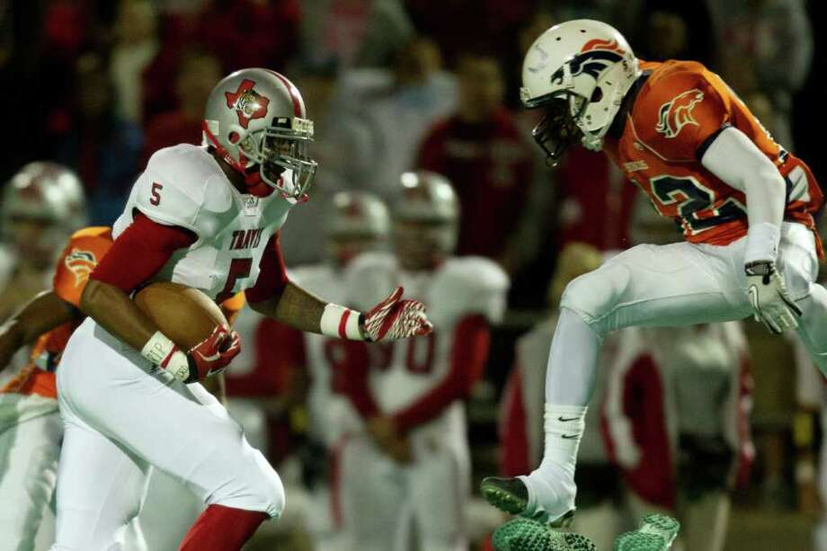 Travis running back Dequarious Davis (5) faces the defense of Bush defensive back Prince Ene (12) during the first quarter of a high school football game at  Mercer Stadium, Saturday, Oct. 29, 2011, in Sugar Land. Photo: Smiley N. Pool, Houston Chronicle / © 2011  Houston Chronicle