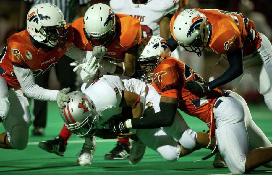 Travis running back Deven Scoby (10) is brought down by a host of Bush defenders during the first half of a high school football game at  Mercer Stadium, Saturday, Oct. 29, 2011, in Sugar Land. Photo: Smiley N. Pool, Houston Chronicle / © 2011  Houston Chronicle
