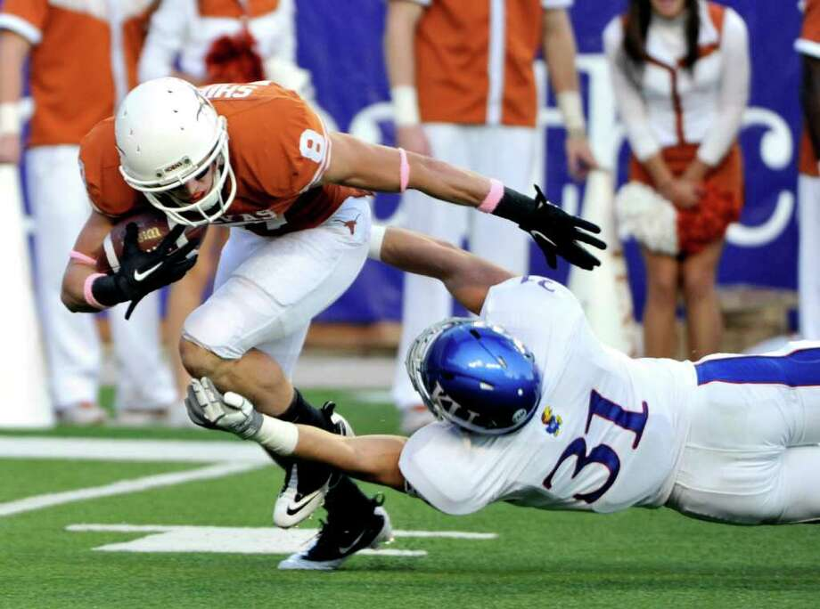 Texas' Jaxon Shipley, left, is tackled by Kansas' Ben Heeney, right, as he tries to return a punt in the first quarter during an NCAA college football game, Saturday, Oct. 29, 2011, in Austin, Texas. Photo: AP