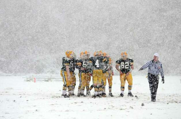 Snow falls as the Trinity Catholic High School football team walks out onto the field during the football game against Bassick at Trinity Catholic High School in Stamford on Saturday, Oct. 29, 2011. Photo: Amy Mortensen / Connecticut Post Freelance