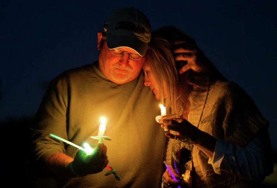"Tom and Janelle Murray embrace during a prayer vigil for their missing son, Thomas ""T.J."" Murray, at Oak Ridge High School Saturday, Oct. 29, 2011 in Conroe. Murray was last seen leaving a sports bar on Sawdust Road in Montgomery County just after midnight Oct. 19. Photo: Brett Coomer, Houston Chronicle / © 2011 Houston Chronicle"