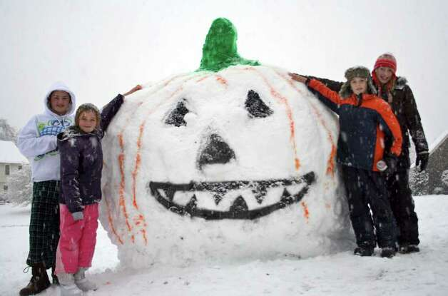 Making the best of a snowy Halloween are, from left, Megan,12, and Kate, 8, Goyda and Sami, 12, and Sean, 10, Arnold. All four kids created a Pumpkin built of Snow. The kids and the Snow Pumpkin live on Bishop Circle in Sandy Hook. Photo by Ellen Goyda Photo: Contributed Photo