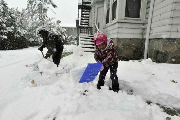 Manuel Parlez and his daughter Gina Parlez, 6, work to remove snow from their walkway in Danbury on Saturday, Oct. 29, 2011. Photo: Jason Rearick