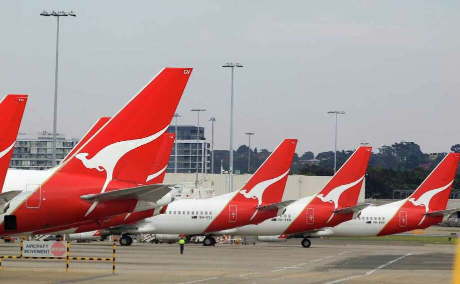 FILE-- The tails of Qantas planes are lined up at Sydney Airport in Sydney, Sunday, Oct. 30, 2011. A Qantas Airways Ltd. A380 superjumbo suddenly lost altitude for about 10 seconds more than 30,000 feet above the Pacific Ocean after flying through the wake of another plane. Photo: Rick Rycroft / AP