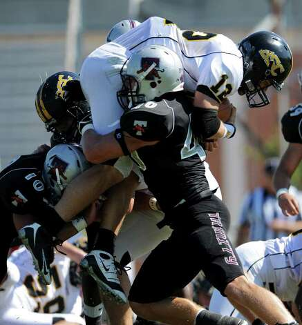 Trinity's Thomas Puskarich (40) lifts Birmingham Southern quarterback Jimmy Stainback (12) off the ground during a NCAA Division III football game between Birmingham Southern and Trinity University In San Antonio, Texas on October 28, 2011.