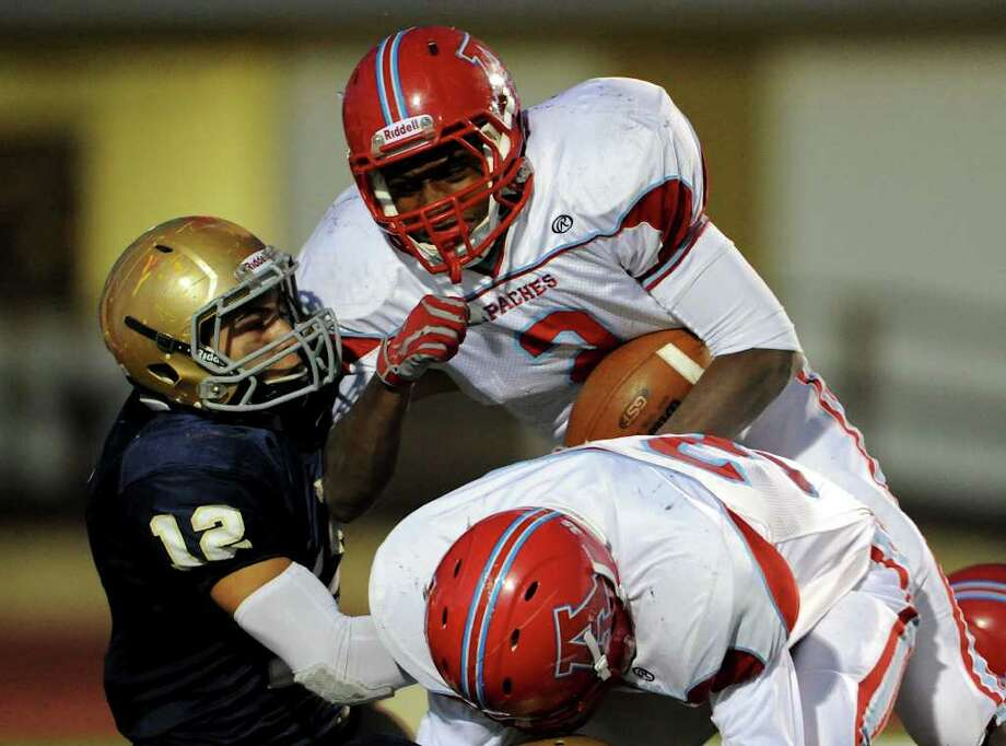 Antonian junior running back Sterling Holmes (2) tries to push his way past Holy Cross linebacker Manuel Hurtado during a TAPPS 2-I football game between Antonian and Holy Cross In San Antonio, Texas on October 29, 2011.