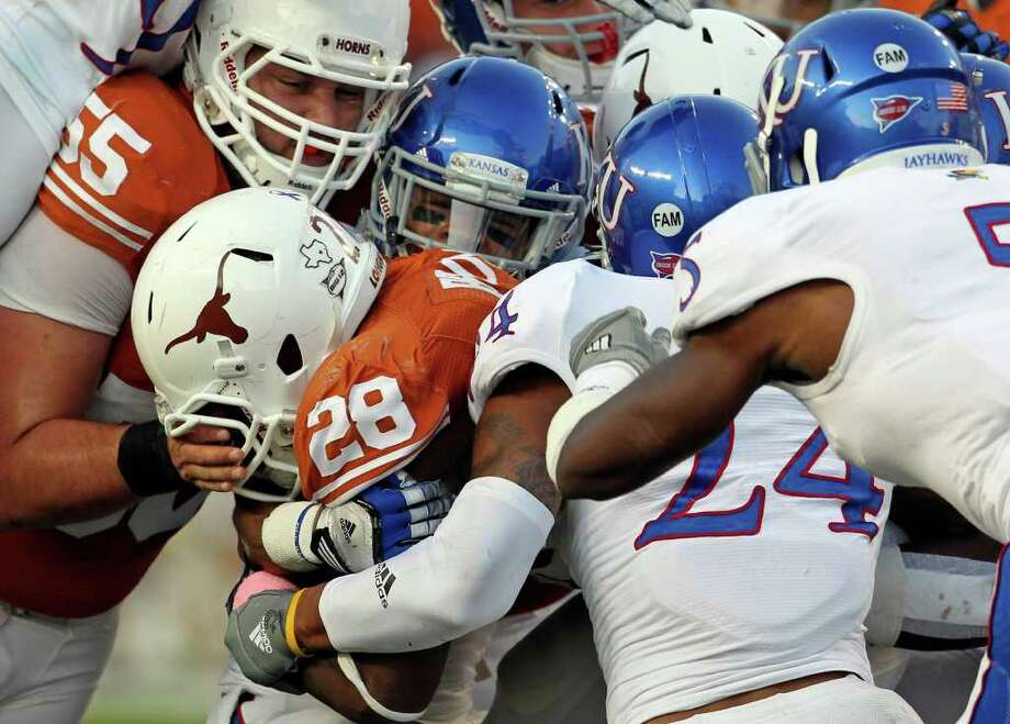 A crowd of tacklers try to squeeze Ut running back Malcom Brown to a stop as Longhorns play Kansas at Darrell K. Memorial Stadium on  October 29, 2011.  Tom Reel/Staff Photo: TOM REEL, Express-News / © 2011 San Antonio Express-News