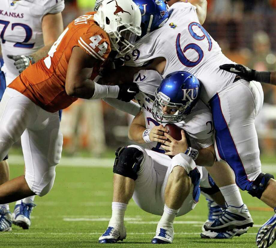 KU quarterback Jordan Webb finds himself trapped under his own lineman as UT defender Jackson Jeffcoat moves in for the kil in the fourth quarter as Longhorns play Kansas at Darrell K. Memorial Stadium on  October 29, 2011.  Tom Reel/Staff Photo: TOM REEL, Express-News / © 2011 San Antonio Express-News