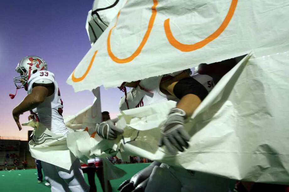 Travis running back R.J. Noriega (33) is the first to break through the banner as the team takes the field to face Bush in a high school football game at  Mercer Stadium, Saturday, Oct. 29, 2011, in Sugar Land. Photo: Smiley N. Pool, Houston Chronicle / © 2011  Houston Chronicle