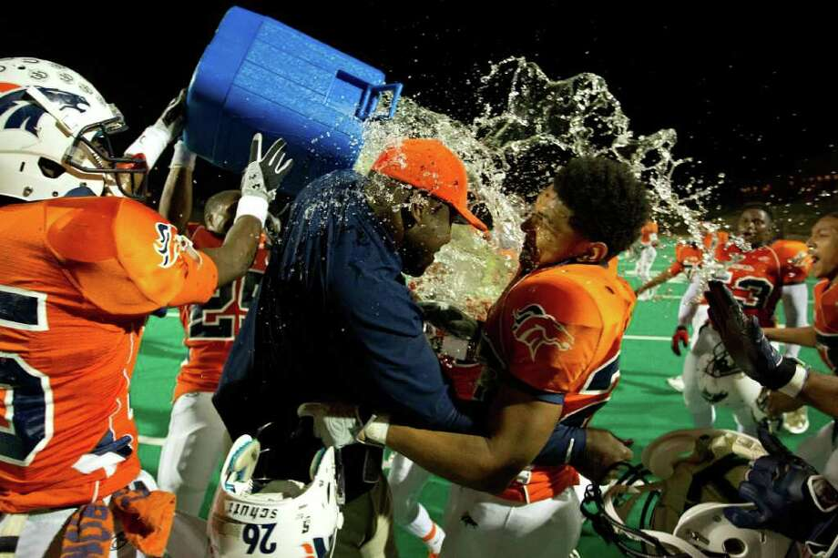 Bush head coach Allen Aldridge is doused by his players after the Broncos defeated Travis in a high school football game at  Mercer Stadium, Saturday, Oct. 29, 2011, in Sugar Land. Photo: Smiley N. Pool, Houston Chronicle / © 2011  Houston Chronicle