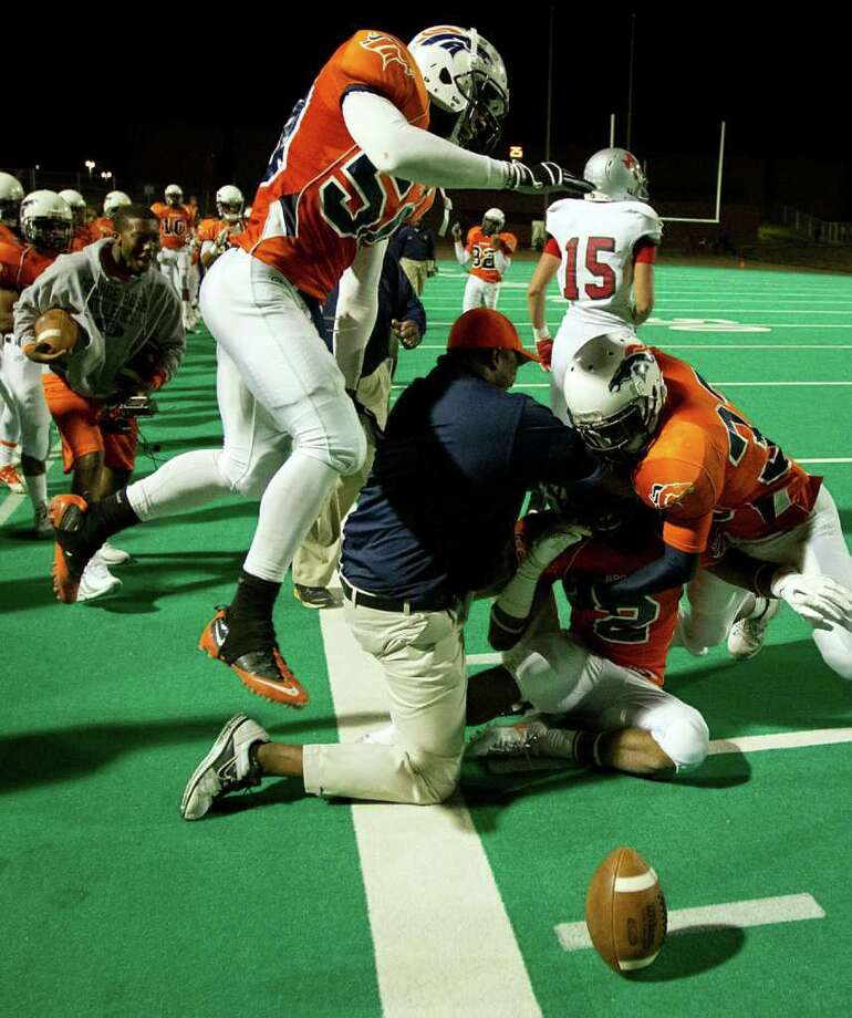 Bush players and coaches pile on to defensive back Darius Reed (2) after his interception in the final seconds sealed the Broncos victory over Travis high school football game at Mercer Stadium, Saturday, Oct. 29, 2011, in Sugar Land. Photo: Smiley N. Pool, Houston Chronicle / © 2011  Houston Chronicle